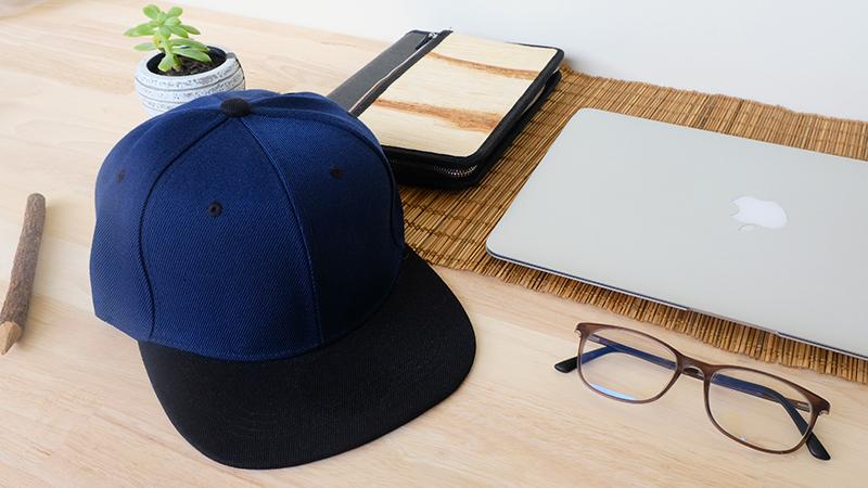 หมวกฮิปฮอป สีกรมท่า ปีกหมวกสีดำ บนโต๊ะทำงาน