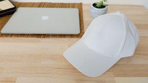 หมวกผ้าพีช สีขาว วางหันข้าง บนโต๊ะทำงาน