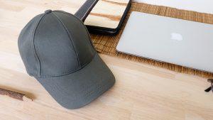 หมวแก๊ปผ้าพีช สีเข้ม วางหันข้าง บนโต๊ะทำงาน